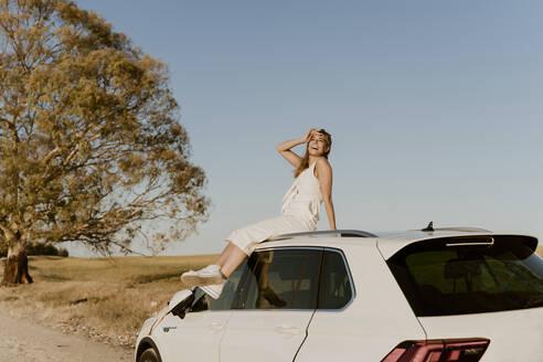 Female traveller sitting on white car roof - ERRF01603