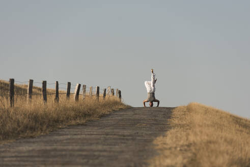 Mid distance view of mature man doing headstand on road against clear sky - KJF00320