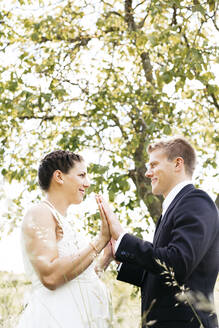 Pregnant bride and her husband holding hands on a meadow - HMEF00475
