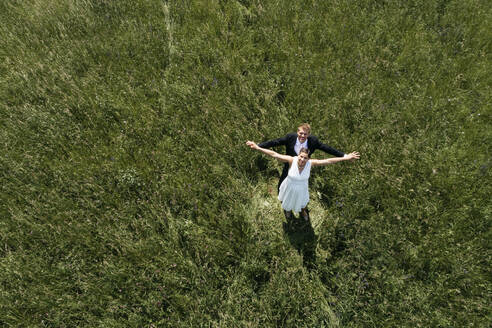Aerial view of pregnant bride with her husband on a meadow - HMEF00484