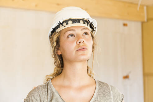 Young woman checking the construction of a new wooden house - TCF06133
