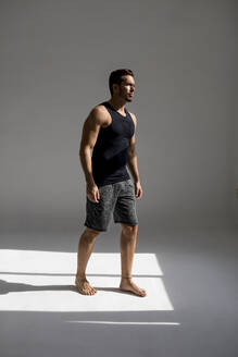Handsome man doing workout in his loft studio home. Barcelona, Spain. - MAUF02609