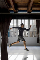 Dynamic athlete jumping in studio loft - MAUF02630