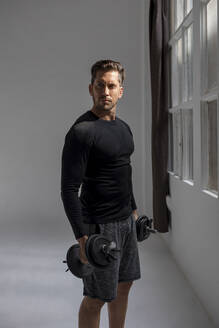 Handsome man doing workout in his loft studio home. Barcelona, Spain. - MAUF02642