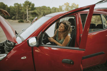 Woman sitting in open car, having a breakdown - DMGF00066