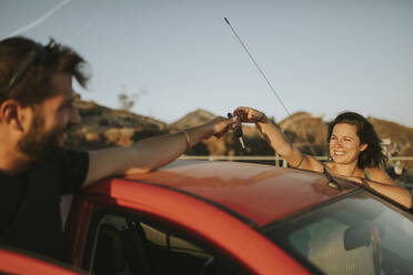 Couple exchanging car keys on a road trip - DMGF00072