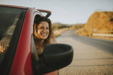 Woman on a road trip looking out of car window - DMGF00078