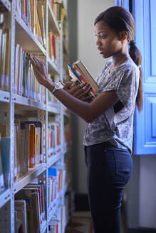 Young woman checking the books at the bookshelves at National library, Maputo, Mocambique - VEGF00391