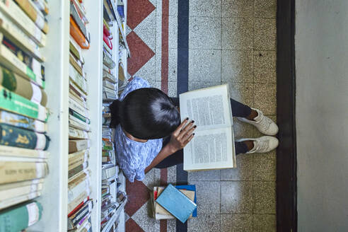 Top view of young woman sitting on the floor reading a book at National library, Maputo, Mocambique - VEGF00394