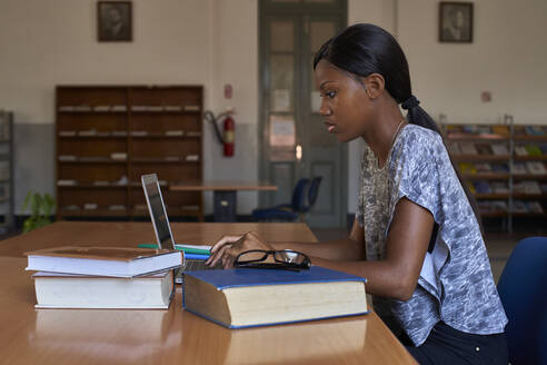 Young student working on laptop at National library, Maputo, Mocambique - VEGF00397