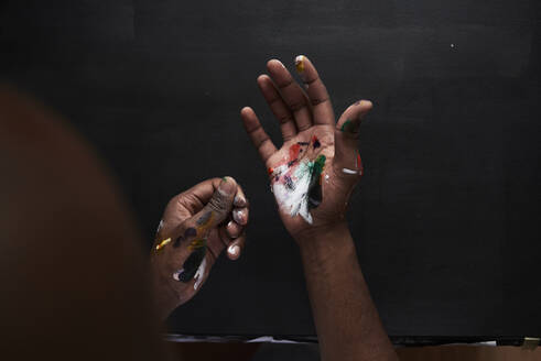 Dirty hands of artist with colorful paints against black background - IGGF01241