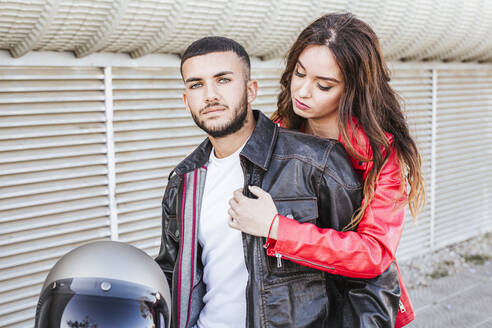Portrait of couple with motorcycle helmet wearing leather jackets - LJF00289