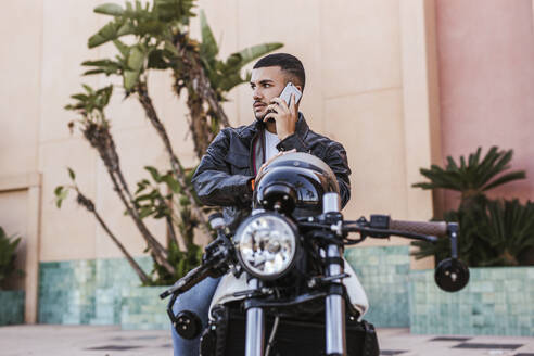 Portrait of young man on the phone sitting on his motorbike - LJF00325