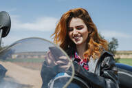 Portrait of happy redheaded woman on motorbike looking at cell phone - LJF00337