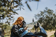 Redheaded woman on motorbike looking at cell phone, Andalusia, Spain - LJF00340