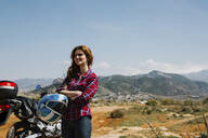 Happy redheaded woman with motorbike enjoying view, Andalusia, Spain - LJF00346