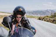 Portrait of motorcyclist putting helmet on, Andalusia, Spain - LJF00361