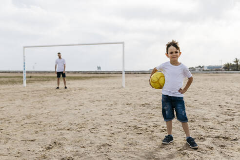 Portrait of boy with football on the beach - JRFF03413