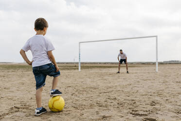 Man and boy playing soccer on the beach - JRFF03416