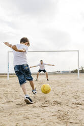Man and boy playing soccer on the beach - JRFF03422