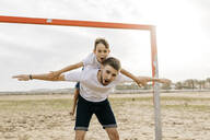 Man and boy celebrating a goal on the beach - JRFF03434