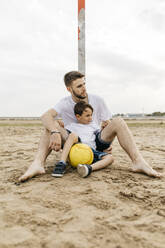 Man and boy resting after soccer game on the beach - JRFF03437