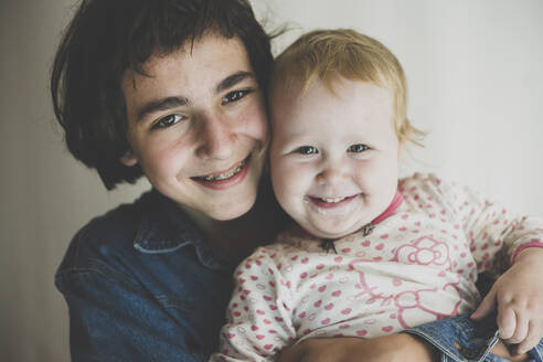 Portrait of happy teenage boy hugging his toddler sister - IHF00166