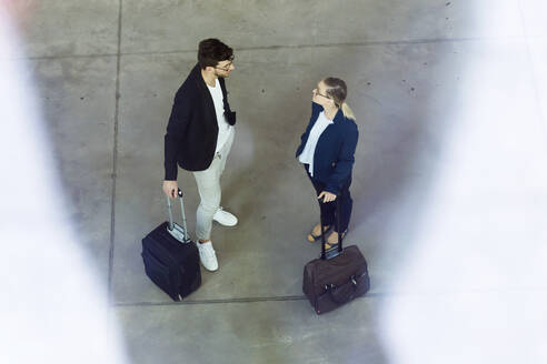 Portrait of two young business partners talking in the airport hall. - JSRF00375