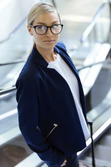 Portrait of beautiful young business woman looking at camera on escalator. - JSRF00378