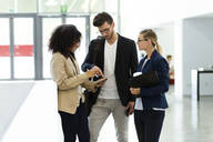 Young business people using a tablet in a foyer - JSRF00384