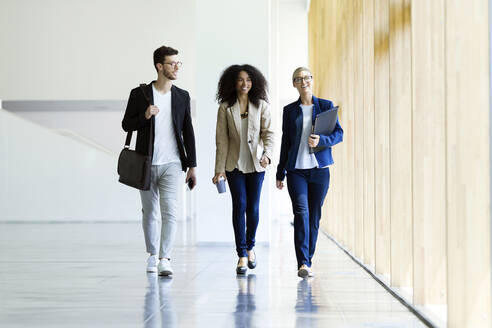 Young business people walking and talking in a hallway - JSRF00390