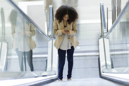 Portrait of beautiful young business woman using her mobile phone on escalator. - JSRF00399