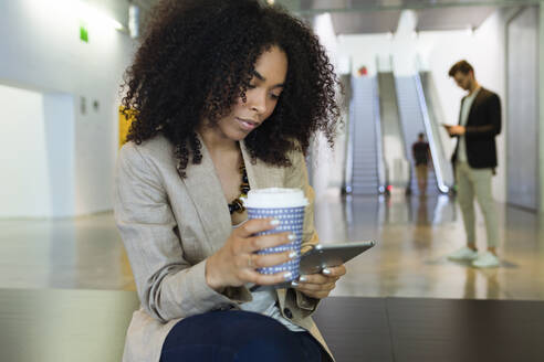 Young businesswoman with takeaway coffee and smartphone in a foyer - JSRF00405