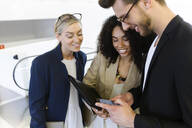 Three young business people sharing a smartphone - JSRF00426