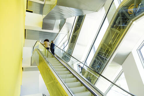 Young business people on an escalator - JSRF00432