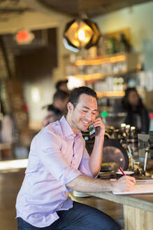 Hispanic businessman talking on cell phone in coffee shop - BLEF08244