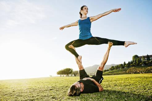 Caucasian couple doing acro yoga in park - BLEF08271