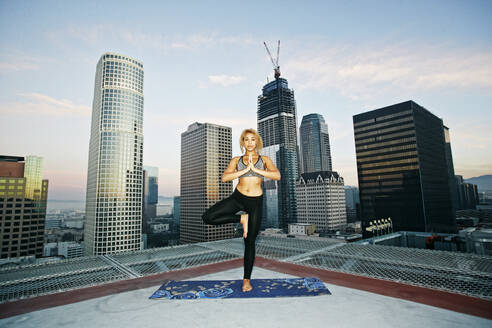Mixed race woman practicing yoga on urban rooftop - BLEF08274
