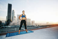 Mixed race woman practicing yoga on urban rooftop - BLEF08277