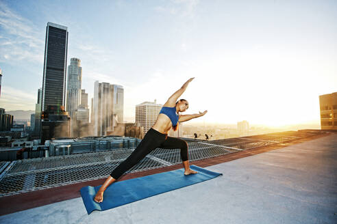 Mixed race woman practicing yoga on urban rooftop - BLEF08280