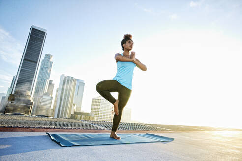 Black woman practicing yoga on urban rooftop - BLEF08286