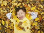 Toothless Hispanic boy laying in autumn leaves - BLEF08325