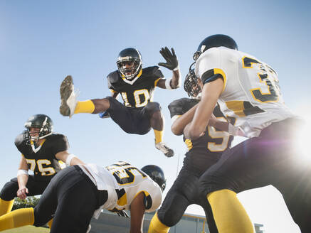 Football player leaping over players on football field - BLEF08427