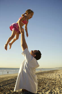 Father lifting daughter in air on beach - BLEF08445