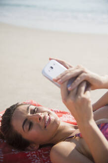 Caucasian woman using cell phone on beach - BLEF08596