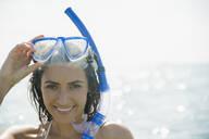 Caucasian woman wearing snorkel and mask in ocean - BLEF08605