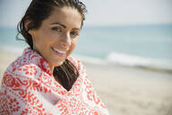 Caucasian woman wrapped in towel on beach - BLEF08608