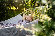Germany, Bavaria, Landshut, Girl relaxing in hammock in garden - SARF04323