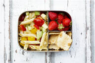 Pasta salad, strawberries and crackers in lunch box on wooden table - LVF08126