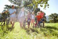 Multi-generation family pushing mountain bikes in rural field - JUIF02008